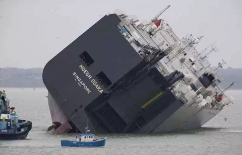 The cargo ship Hoegh Osaka lies on its side